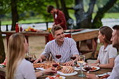 friends having picnic french dinner party outdoor during summer holiday