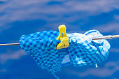Bathing suit drying on clothesline, blur sea background.