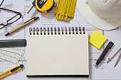 Residential building drawings and blank notepad on an office desk. Construction concept.