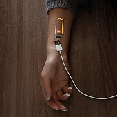 Low battery symbol drawn on human hand. USB cable to recharge