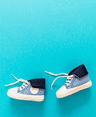 Baby boy shoes on blue color background, copy space