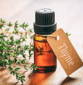 Thyme essential oil and fresh leaves on wooden background