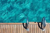Sailing boat stern deck, teak wood and metal ladders, turquoise blue sea water background.
