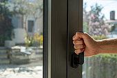 Aluminum window frame detail. Male hand opens the metal door closeup view.