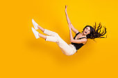 Full length body size photo of woman wearing casual clothes falling down isolated on vibrant yellow color background