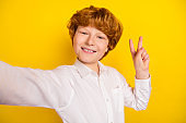 Photo of young smiling good mood handsome boy take selfie showing v-sign isolated on yellow color background