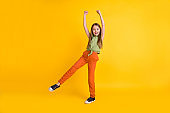 Full length body size photo little girl wearing casual clothes smiling gesturing like winner isolated vivid yellow color background