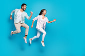 Photo of charming young couple wear casual shirt jumping running empty space isolated blue color background