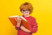 Photo of young focused serious redhead boy look hold hands book reader isolated on yellow color background