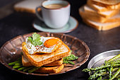Fresh sandwiches with fried egg served on a vintage metallic plate, horizontal