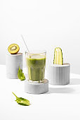 Conceptual creative still life with green fruits and smoothie on concrete podiums over white background