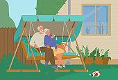 Senior Couple Resting In Garden Swing In The Backyard.