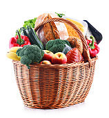 Wicker basket with assorted grocery products isolated on white