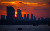 Sun setting behind skyscrapers creating a silhouette of London cityscape at Masthouse Terrace Pier