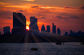 Sun setting creating a silhouette of London cityscape and sun rays at Masthouse Terrace Pier