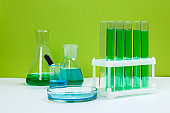 Various laboratory glass items with water and empty on white table with green background