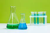 Laboratory glassware with solutions of different colors on table