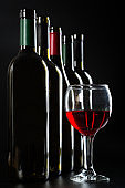 elegant Wine bottles and a glass with red wine on a dark glossy background.