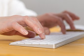 An image of a woman's hand is typing on a white keyboard on a wooden table. Selective focus