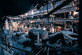Large abandoned metallurgy factory workshop, hangar or warehouse inside, dirty spooky and rusty building