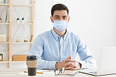 Young employee or teacher sitting in the office, wearing medical mask, practicing social distancing because covid safety protocol