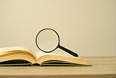 Magnifying glass and open book on the desk, education concept, copy space