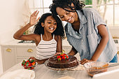 African mom and daughter making cake at home