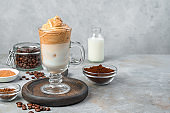 Dalgona iced coffee on a gray vintage background. Coffee foam with milk and ice