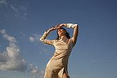 Fashion outdoor portrait of woman in beige silk satin long dress against clear blue sky