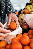 man at the greengrocer uses a reusable mesh bag