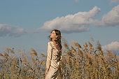 Fashion outdoor portrait of woman in beige silk satin long dress.