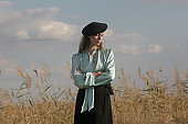 Fashion outdoor portrait of woman in mint silk blouse, black skirt and beret