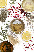 Herbal tea, top view. Dry herbs, lemon slices and tea cups on white. Herbs in bulk, zero waste and eco-friendly lifestyle, herbal medicine concept.