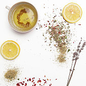 Herbal tea, top view with copy spce. Dry herbs, lemon slices and tea cups on white. Herbs in bulk, zero waste and eco-friendly lifestyle, herbal medicine concept.