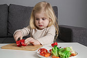 Portrait of adorable toddler girl preparing healthy meal, cutting vegetable with knife.