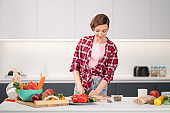 Pretty housewife cutting fresh carrot cooking dinner for her family wearing a plaid shirt. Cooking with passion young woman with short hair standing at modern kitchen. Healthy food leaving - concept