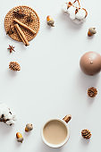 Autumn composition. Coffee cup, candles, cotton, cinnamon sticks on white background. Autumn, fall concept. Flat lay, top view, copy space