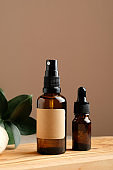 Set of natural organic SPA beauty products on wooden board. Amber glass spray bottle, homemade soap, serum, and green leaf. Bio cosmetics branding, packaging design.