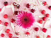 Cherry berry pattern with flowers and petals in water on pink background