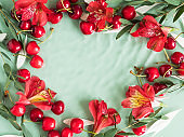 Cherry frame with red flowers and petals in water on natural green background