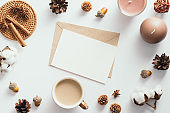 Autumn feminine desk table with romantic letter, coffee cup, candles, pine cones, cotton, cinnamon sticks on white background. Flat lay, top view.