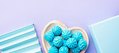 Blue turquoise meringue on heart shaped dish with gift box and decor on pastel purple background