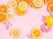 Summer vibe orange citrus slice fruit texture background on pastel pink with wet spots