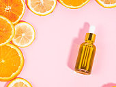 Vitamin C serum bottle with dropper on pink background with orange citrus slices