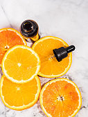Vitamin C serum bottle with dropper on white marble background