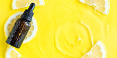 Dark glass essential oil, serum bottle on yellow lemon slice summer background with water ripples