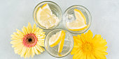 Lemon water drink with ice cubes on stone background with gerbera daisy yellow flowers