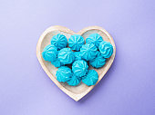 Heart shaped wooden dish with blue sweet meringues