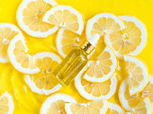 Glass essential oil, serum bottle on summer background with yellow lemon slice in water with ripples