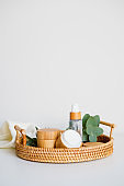 Natural cosmetics set in eco-friendly bamboo packaging in rattan tray with eucalyptus and towel. SPA, bath beauty products. Moisturizer cream, lotion.
